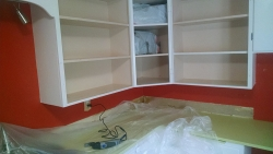 Here I\'m getting ready to trim off the bottom shelves of these low cabinets, using a multi-tool.