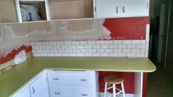 Here we have the beginning of the subway tile installation.  The wall where the cabinets once were has been smoothed.