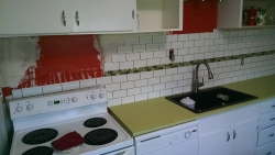 This shows the continuation of the subway tile as it goes behind the refrigerator.