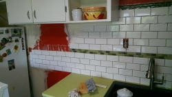 Continuation of the subway tile, going behind the refrigerator.