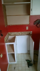 Deconstructing and recycling the plywood to make room for the refrigerator.