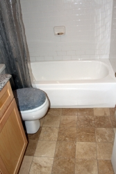 Travertine floor and subway tile bathtub surround