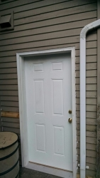 Here is the new door, with the siding replaced.  Note:  Care was taken in caulking all threshold seams.